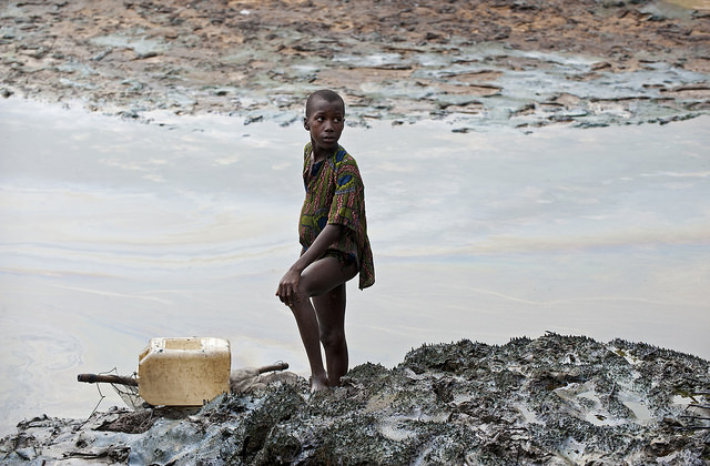 Child-standing-at-oil-polluted-river-banks-in-Goi.jpg